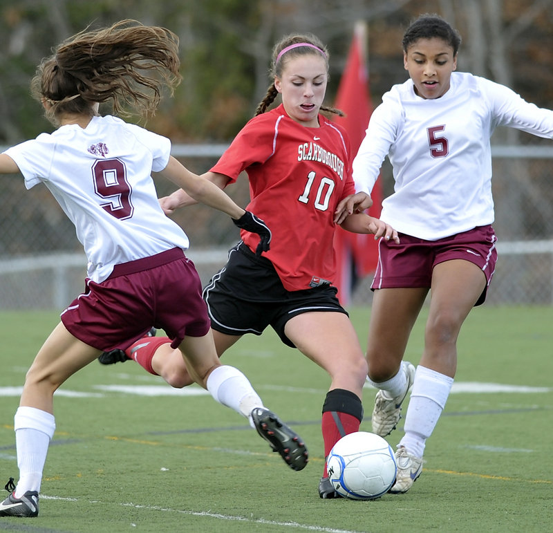 Jessica Meader of Scarborough tries some fancy footwork to get past Bangor defenders Anna-Maria Dagher, left, and Denae Johnson during the Red Storm's win in the Class A final.
