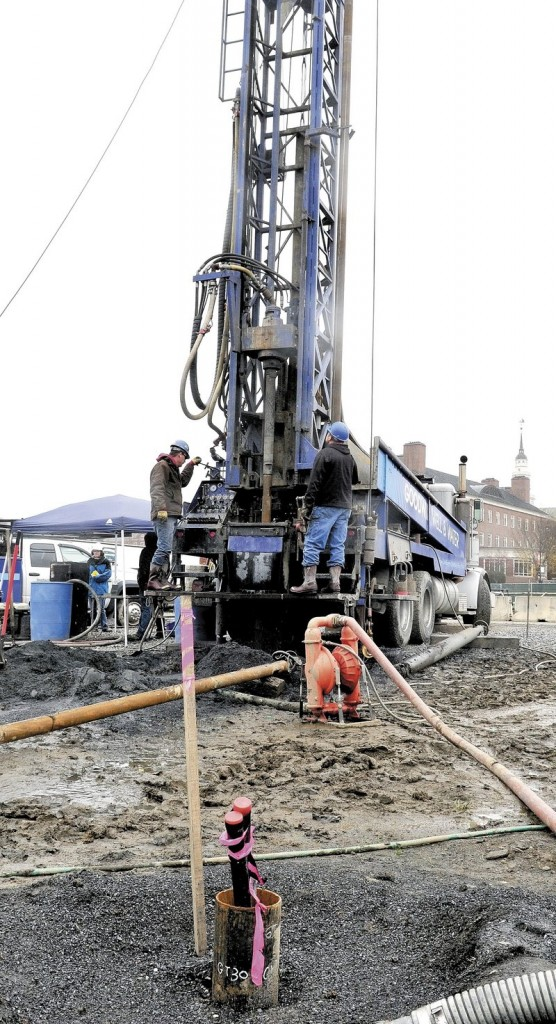 Workers drill holes to install the geothermal system that will help heat the new science building at Colby.