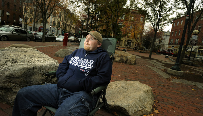 "Chris ""Benji"" Levine, 24, of Portland, waits for customers Monday at his hot dog stand on Middle Street. Levine says he favors Mitt Romney over President Obama, but he is most concerned that the same-sex marriage question passes."