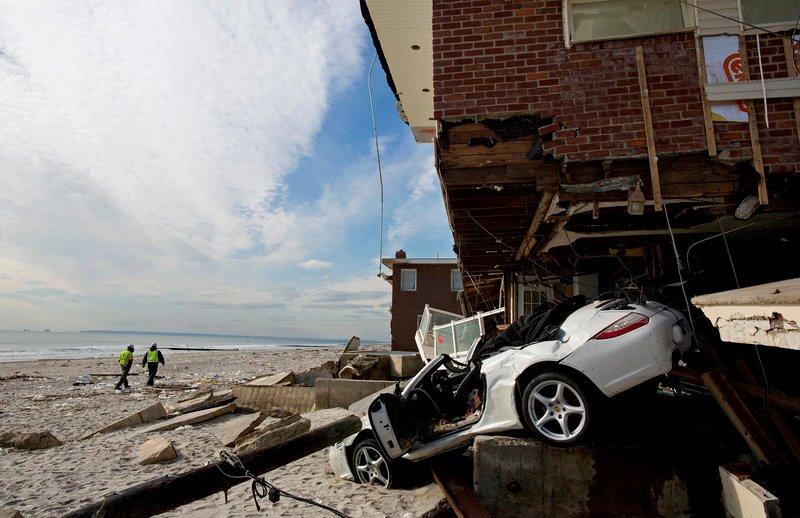 A vehicle sits embedded in a badly damaged home along the beach in the Belle Harbor section of the New York City borough of Queens on Monday in the wake of Superstorm Sandy. Tens of thousands of people without power along the ravaged Atlantic coastline faced the prospect of finding somewhere else to stay.
