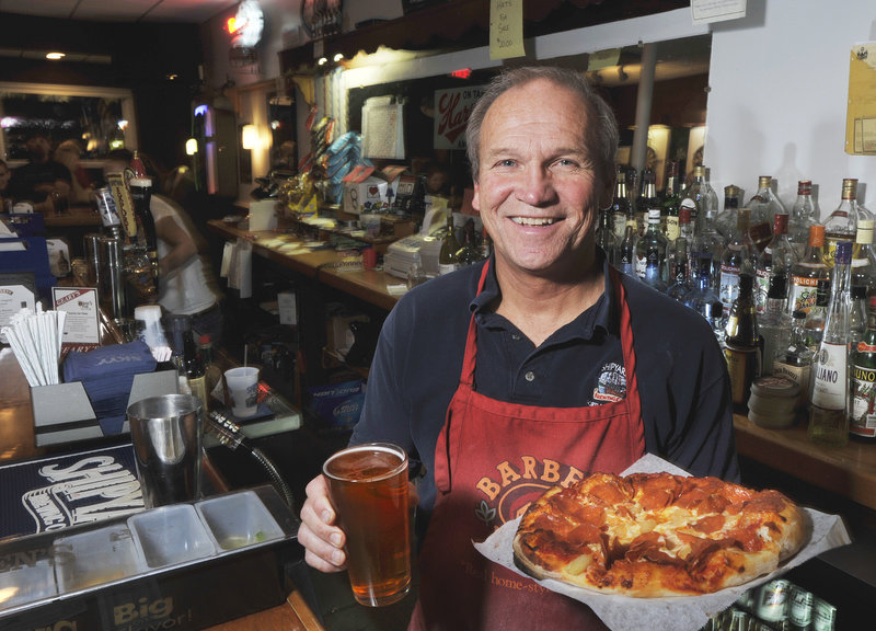 Howie Chadbourne, owner of Howie's Pub in Portland's East Deering neighborhood, offers up a draft beer and a pizza.