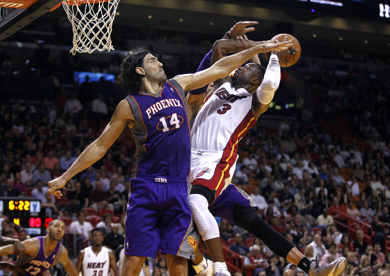 Dwyane Wade of the Miami Heat tries to get a shot over the Phoenix Suns' Luis Scola on Monday night. Long a defense-first team, the Heat have so far been far from the stingy outfit that won the NBA title last season.