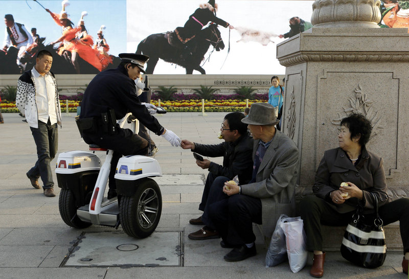 A Chinese police officer checks the identity of Chinese men resting Oct. 24 on Tiananmen Square in Beijing, near the site of the Chinese Communist Party's 18th national Party Congress on Nov. 8. During the once-a-decade political transition, President Hu Jintao and most of the party leadership will begin to hand over power to younger colleagues.