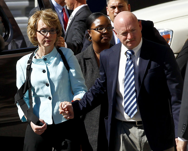 Former Rep. Gabrielle Giffords, left, and her husband, Mark Kelly, leave court after the sentencing of Jared Lee Loughner on Thursday in Tucson, Ariz. U.S. District Judge Larry Burns sentenced Loughner to life in prison for the January 2011 attack that left six people dead and Giffords and others wounded.
