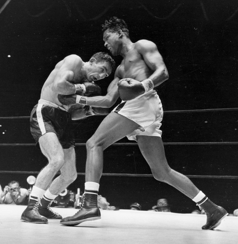 Carmen Basilio, left, bores during his upset of world middleweight champion Sugar Ray Robinson at Yankee Stadium on Sept. 23, 1957.