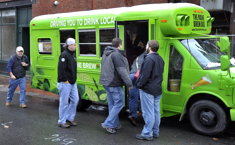 Zach Poole, right, greets tour members as they board the Maine Brew Bus behind the Thirsty Pig for a  2014 tour of two breweries, a meadery, a coffee roaster, a fermenter and distiller over several hours.