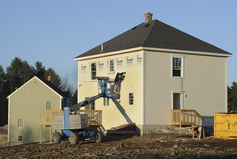 A worker installs siding Friday on a new home in the Sunrise Ridge subdivision along the Portland Road in Buxton. In southern Maine, places where construction of new homes has increased substantially since last year include Kittery, Waterboro and Wells.