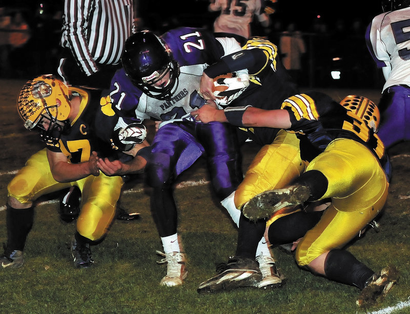 Racean Wood of Waterville looks for room to run Friday night as three Mt. Blue players converge on the tackle during the Eastern Class B championship game at Farmington. Undefeated Mt. Blue won, 42-14.