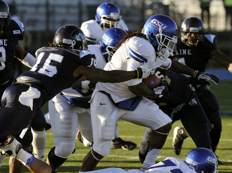 Maine safety Jamal Clay tries to bring down Georgia State running back Roosevelt Watson during's Saturday's game in Orono. Clay had two of Maine's four interceptions in a 51-7 victory.