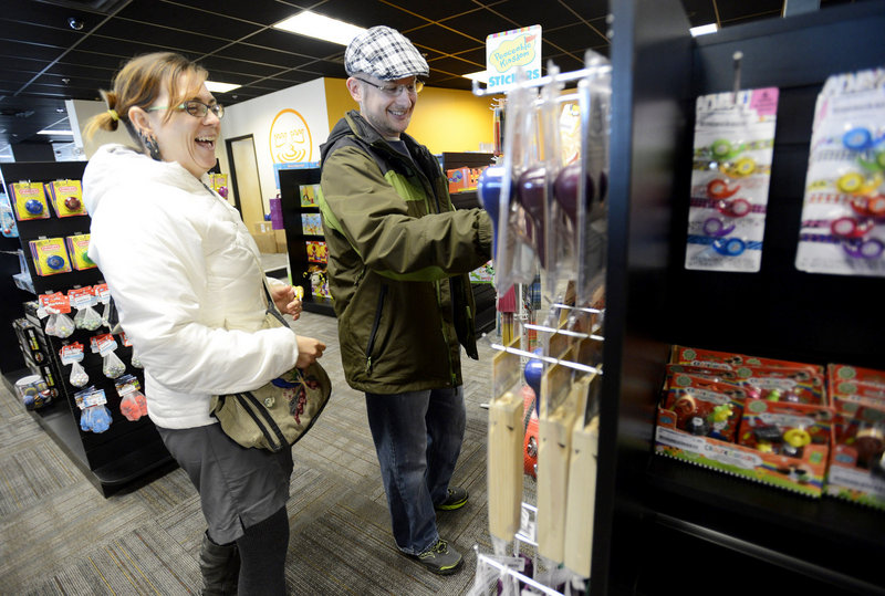 Jessica Wienke and David Wilson of South Portland look over merchandise Wednesday in the toy section of the new Bull Moose store in Mill Creek. It's in the former Blockbuster building on Waterman Drive.