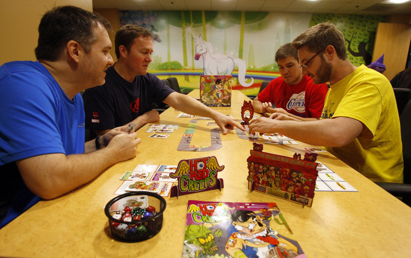 From left, Kyle Heuer, Matt Hyra, Will Brinkman and Phil Cape play Hot Rod Creeps, a card-driven racing game at Cryptozoic Entertainment in Irvine, Calif. The revival of board games has been driven in part by fans of digital games.