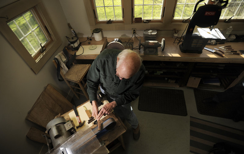 "Bruce Bohrmann fashions the handle of a knife in his Yarmouth workshop earlier this month. ""I can start working on a blade and I can tell immediately if it's going to love me or hate me,"" Bohrmann said. ""The steel talks to me, and I swear back at it."""