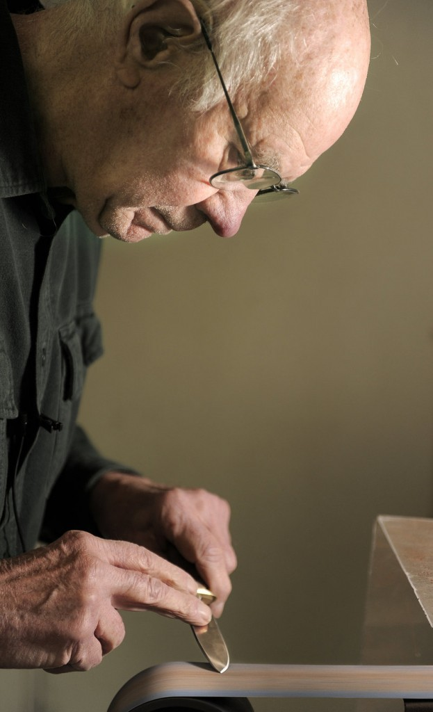 Bruce Bohrmann sharpens a knife in his Yarmouth workshop earlier this month.