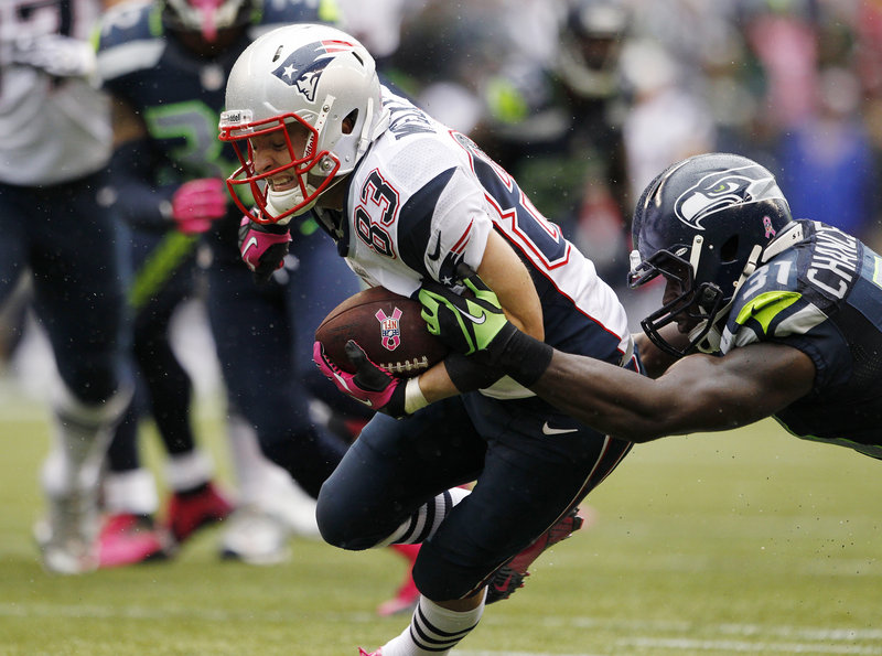 Wes Welker, shown here trying to break from the grasp of a Seattle Seahawk, has caught 66 passes this season, just three behind NFL leader Reggie Wayne, whose Colts come to Foxborough on Sunday.