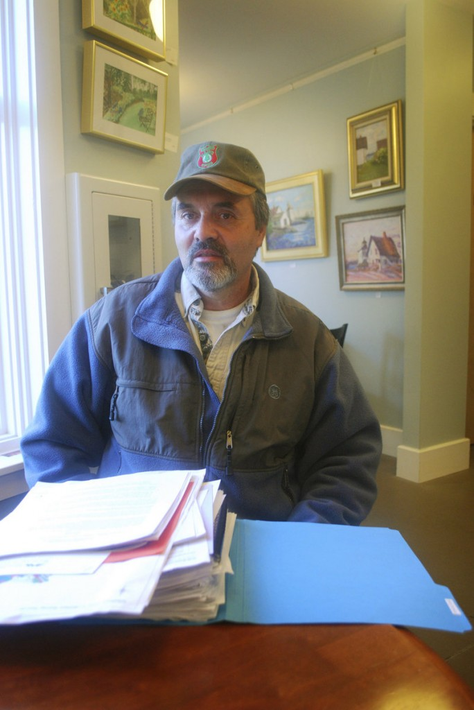 "Fred Thomas sits behind a year's worth of research that he collected as chairman of the Islesboro Deer Reduction Committee. ""It's been quite a task,"" Thomas said."