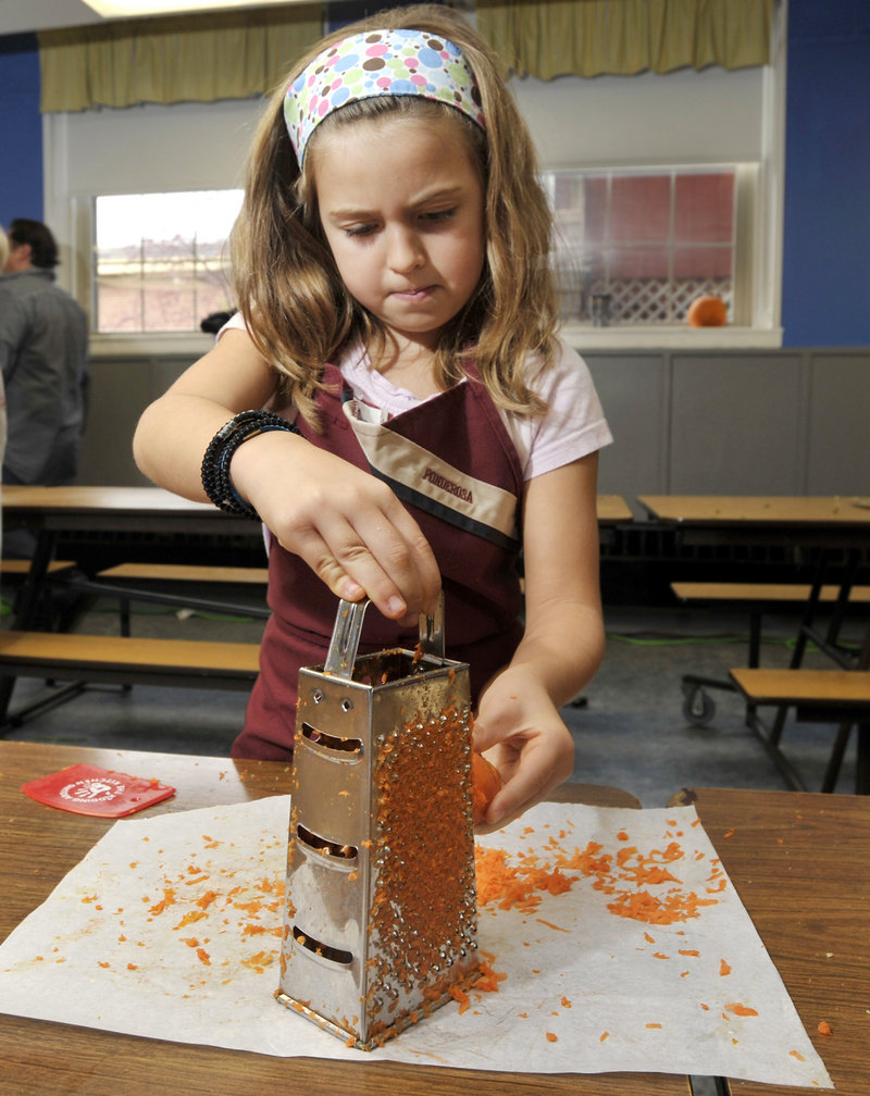 Second-grader Abby Simonelli helps make carrot slaw during a recent lesson on healthy eating at South Berwick Central School. A reader praised Avery Yale Kamila's column about the lessons, but was puzzled when the column ran the same day as an article including a recipe that used sugar and butter.