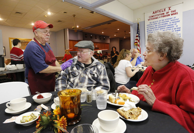 Host Carl Hubbard checks in on Jim and Carol Allen of South Portland on Thursday during the 17th annual Thanksgiving dinner held at VFW Post 832 in South Portland.