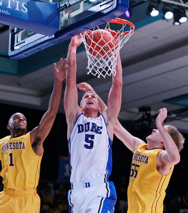 Duke's Mason Plumlee dunks against Minnesota's Andre Hollins, left, and Elliott Eliason during the Blue Devils' 89-71 win in the Battle 4 Atlantis at Paradise Island, Bahamas.