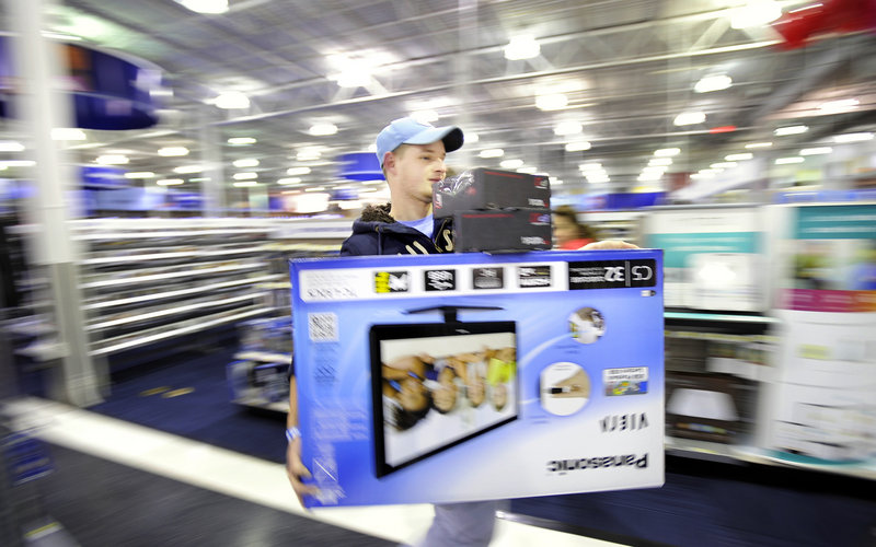 Cory Albert of Lebanon, Conn., races to the Best Buy checkout with a 32-inch television and a couple of headsets just after the store opened on Black Friday. In addition to the mall's anchor stores, 58 venues in the mall area opened their doors at midnight.