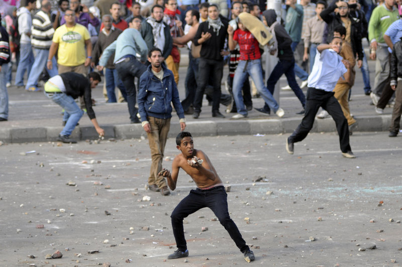 The Associated Press Protesters hurl stones during clashes between supporters and opponents of President Mohammed Morsi in Alexandria, Egypt, on Friday, the day after Morsi granted himself sweeping new powers that critics fear can allow him to be a virtual dictator. Thousands from the two camps threw stones and chunks of marble at each other outside a mosque.