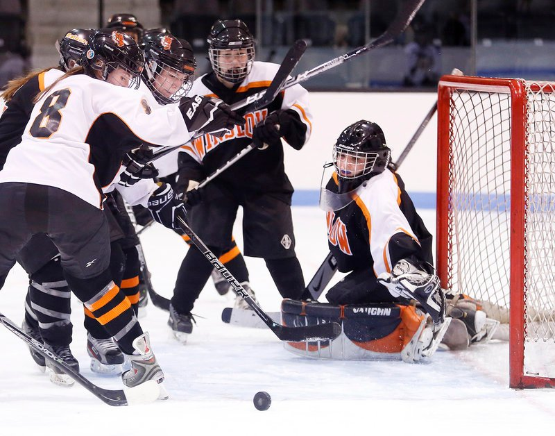 Photos by Derek Davis/Staff Photographer Jessica Cain, whose goaltending kept Winslow in the game Friday night, keeps her eye on the puck as Grace Rabinowitz, left, and Rachel Maroney of Brunswick swoop in for a rebound. Cain made 32 saves in a 4-3 victory to open the season. Brunswick held a 49-23 advantage in shots.