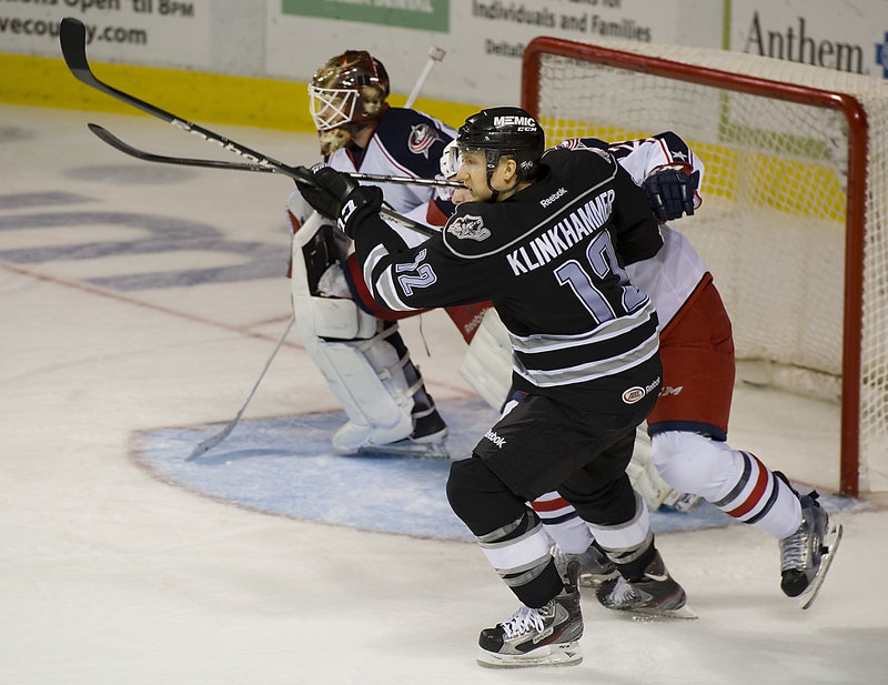 Rob Klinkhammer of the Portland Pirates attempts to gain position in front of the Springfield net while being checked by Theo Ruth of the Falcons. The goalie is Curtis McElhinney.
