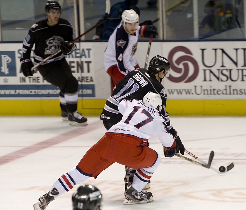 Chris Brown of the Portland Pirates knocks the puck into the Springfield zone past Sean Collins of the Falcons.