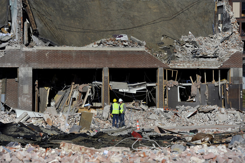 Inspectors work amid debris Saturday after a natural gas explosion leveled a strip club in Springfield, Mass., on Friday evening. The blast damaged 42 buildings and injured 18 people.