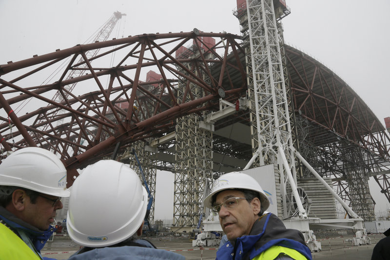 Workers assist Tuesday in the raising of a gigantic steel arch to cover remnants of the exploded reactor at the Chernobyl nuclear power plant. The new safe confinement will cover a hastily built sarcophagus erected shortly after the world's worst nuclear accident in 1986.