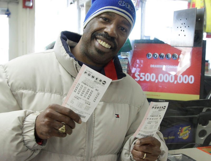 Lamar Fallie, 52, of Chicago buys six Powerball tickets at a BP gas station Wednesday in Calumet Park, Ill. He is unemployed and was lured by the $550 million jackpot.