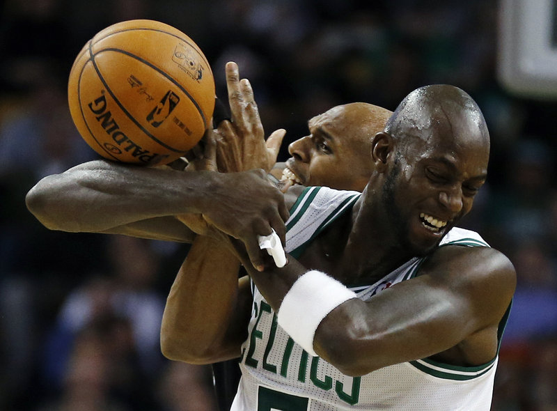 Kevin Garnett of the Celtics gets tangled with Jerry Stackhouse of the Nets while trying to control the ball.