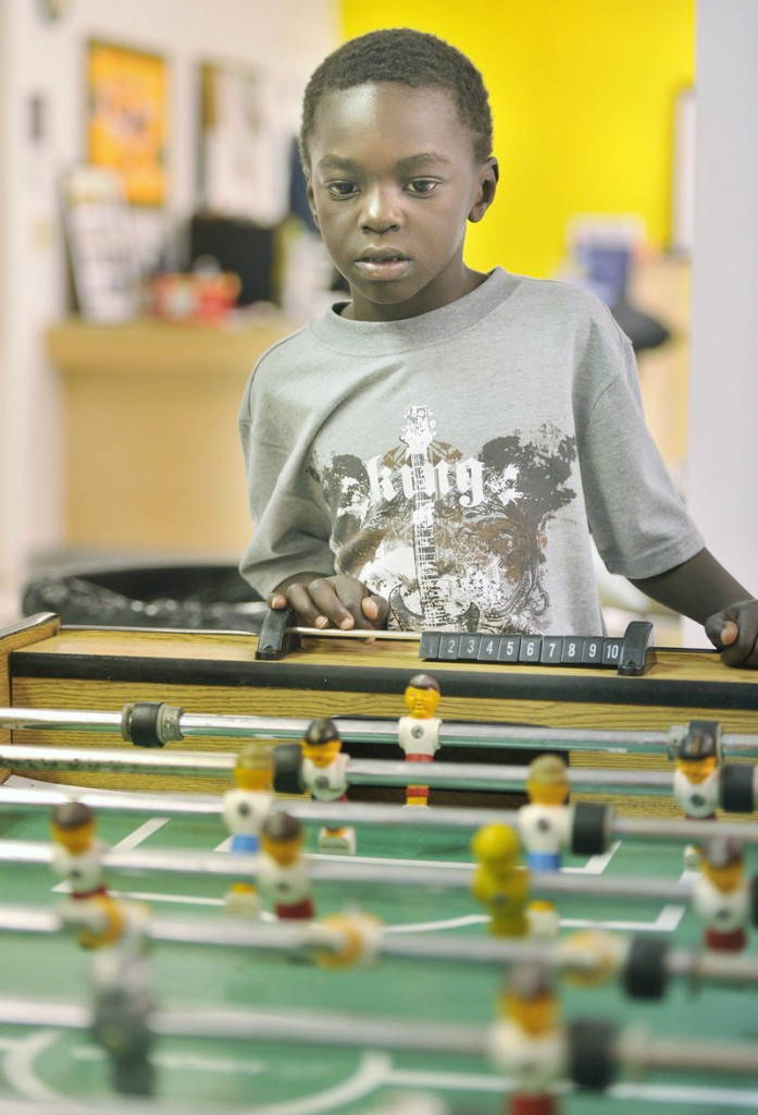 Jamal Ali closely watches a game of FoosBall on Thursday afternoon at the Clubhouse.