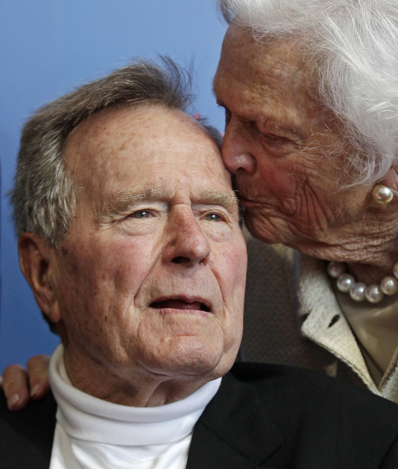 Former President George H.W. Bush gets a kiss from the former first lady. Doctors say they want to keep him hospitalized until the cough goes away.