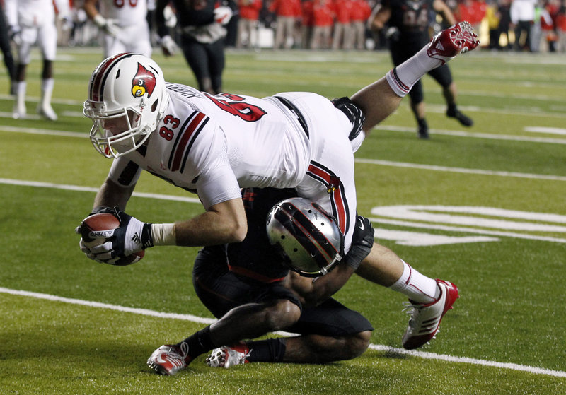 Ryan Hubbell, Louisville tight end, lunges over a Rutgers defender during first-half action of Thursday night's game in Piscataway, N.J., won by the Cardinals.