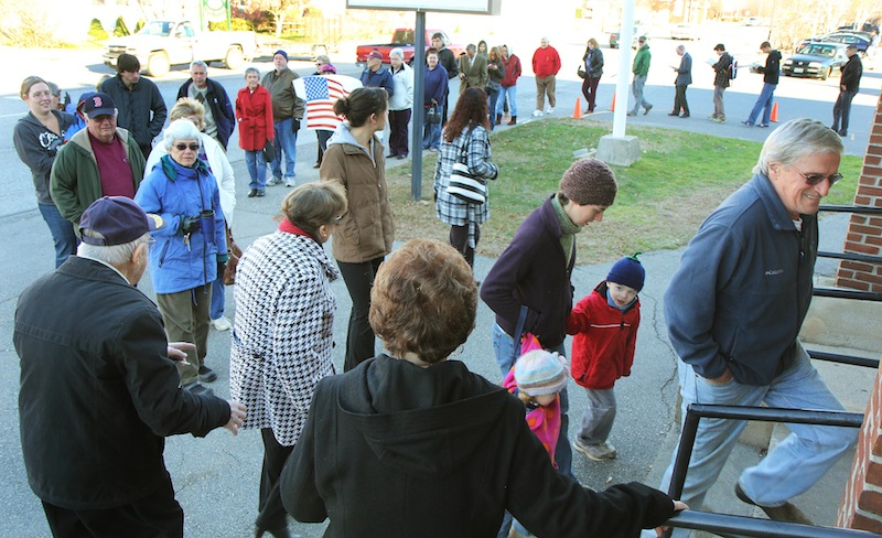 LINING UP TO VOTE: A long line of voters extends out the door of the Bourque-Lanigan American Legion Post 5 shortly after the polls opened in Waterville on Tuesday. High voter turn out is expected today.