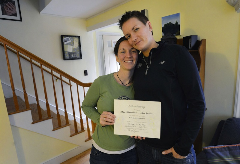 Alisson Poisson and Maggie Oechslie of South Portland hold a marriage certificate that Maggie's father made and presented to them in June 2011. Now that it's law, the couple looks forward to getting a legal certificate. Falmouth and Portland have said they will open at midnight Dec. 29 to accommodate requests from residents eager to get married at the earliest possible moment.