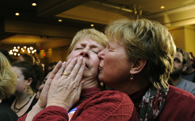 Ellie MacCallum, left, of Windham, receives a kiss from her partner, Judy Eycleshymer, right, after they learned same sex marriage had passed while at the Mainers United for Marriage party at the Holiday Inn by the Bay Tuesday, November 6, 2012. Marriage licenses for same-sex couples in Maine will be issued beginning Dec. 29.