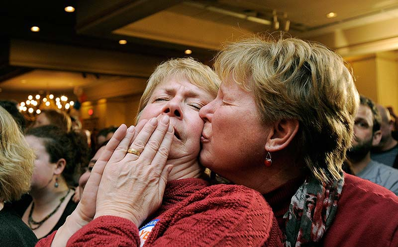 Ellie MacCallum, left, of Windham, receives a kiss from her partner, Judy Eycleshymer, right, after they learned same sex marriage had passed while at the Mainers United for Marriage party at the Holiday Inn by the Bay Tuesday, November 6, 2012. The city of Portland will open City Hall at midnight Dec. 29 to give out marriage license and perform the first same-sex weddings in the state.
