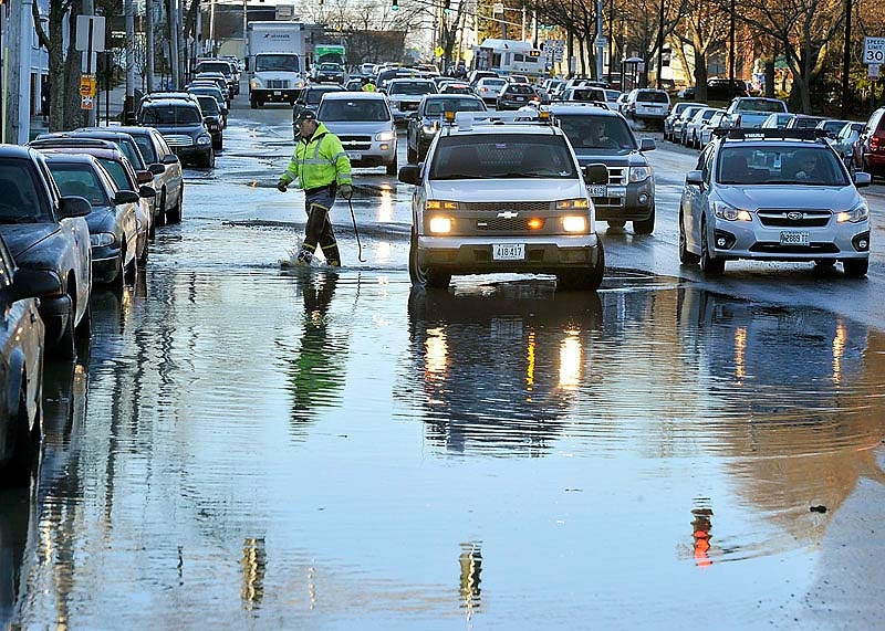Portland Public Service worker Carl Leonard wades through the water as a water main break on Park Avenue near Mellen Street slowed traffic during morning rush hour on Thursday.