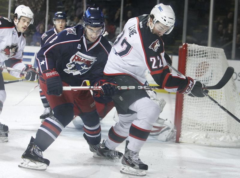 Phil Lane, left, of the Pirates battles with Springfield's Cam Atkinson for the puck. The Pirates won by scoring two goals 26 seconds apart in the third period.