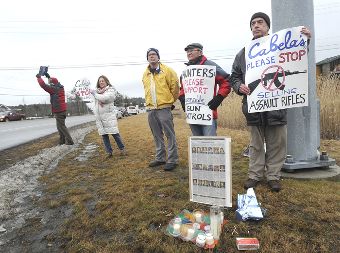 A small group led by Steve Swift of Vassalboro, right, protests the sale of assault rifles at Cabela's in Scarborough on Friday