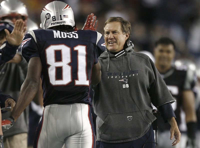 "In this Sept. 16, 2007 file photo, New England Patriots head coach Bill Belichick, right, congratulates wide receiver Randy Moss (81) after his second touchdown catch in the third quarter of an NFL football game against the San Diego Chargers in Foxborough, Mass. Moss arrived at the Patriots five years ago thinking he knew a lot about football. Then, he began playing for Belichick. Moss' mindset regarding his own football knowledge changed in a hurry. Only then did he learn the intricacies of his sport from ""A to Z,"" as the 49ers wide receiver now puts it. (AP Photo/Winslow Townson, File) NFL"