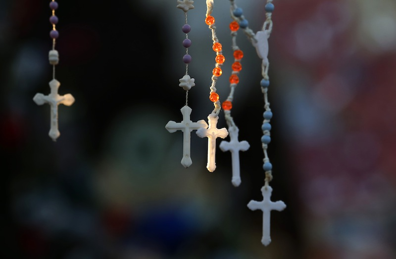 Rosaries are lit by the morning light on a makeshift memorial near the town Christmas tree in the Sandy Hook village of Newtown, Conn., Wednesday. The memorial, which was put up in the aftermath of the elementary school shooting that shocked the small town, is increasing in size as the days go on.