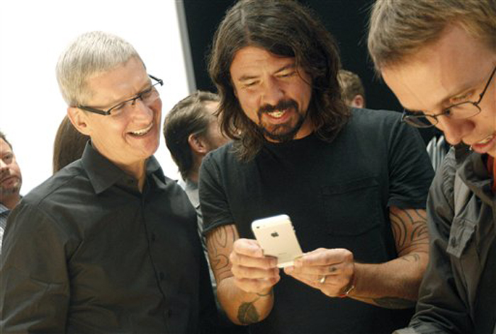 Apple CEO Tim Cook, left, talks with musician Dave Grohl of the Foo Fighters as they look at an iPhone 5 during an Apple event in San Francisco in September.
