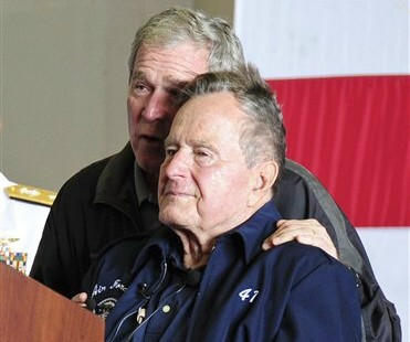 In this June 10, 2012 photo provided by the U.S. Navy, former Presidents George W. Bush, left, and his father, George H.W. Bush, deliver remarks to the crew during a ceremony aboard the aircraft carrier USS George H.W. Bush (CVN 77). Former President George H.W. Bush will spend Christmas in a Houston hospital after developing a fever and weakness following a monthlong, bronchitis-like cough. (AP Photo/U.S. Navy, Petty Officer 2nd Class Maria Rachel D. Melchor)