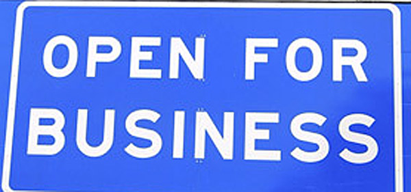 """In this Friday 2011 file photo, an """"Open for Business"""" sign beneath the """"Welcome to Maine"""" sign along Interstate 95 near the New Hampshire border in Kittery. For the third consecutive year, Maine ranked No. 50 in Forbes' seventh annual """"Best States for Business."""""""