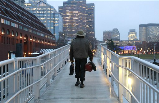 Michael Richard Smith carries a briefcase and a satchel as he walks up a gangway at a wharf in Boston Harbor.