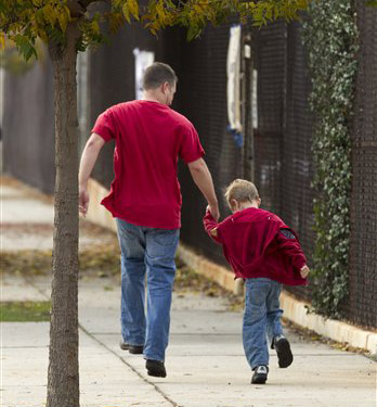 "Tom Fico holds hands with his son Lucas, 5, as they skip on their way to kindergarten in Burbank, Calif., on Monday. New York University child and adolescent psychiatry professor Glenn Saxe says: ""If there is any time to be a little more flexible about routines and rules in support of our children, it is now."""