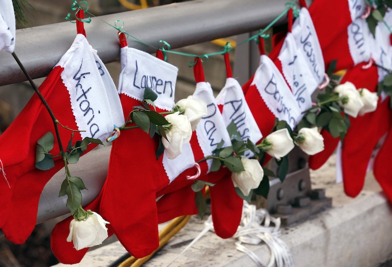 In this Wednesday, Dec. 19, 2012 file photo, Christmas stockings with the names of shooting victims hang from railing near a makeshift memorial near the town Christmas tree in the Sandy Hook village of Newtown, Conn. In the wake of the shooting, the grieving town is trying to find meaning in Christmas. (AP Photo/Julio Cortez, File)