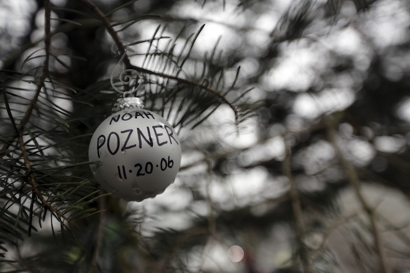 An ornament for Noah Pozner hangs on a tree at one of the makeshift memorials for the Sandy Hook Elementary School shooting, Monday, Dec. 17, 2012 in Newtown, Conn. Pozner was killed when a gunman walked into Sandy Hook Elementary School in Newtown Friday and opened fire, killing 26 people, including 20 children. (AP Photo/Mary Altaffer)